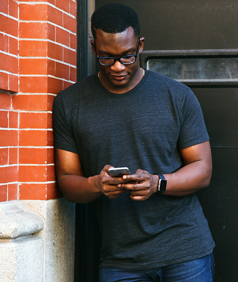 Man Using Phone Leaning Against A Wall