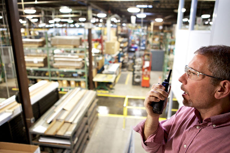 Person Using Walkie Talkie In Warehouse